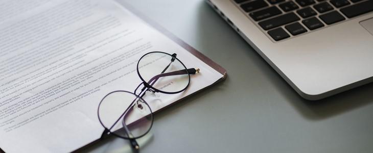 Briller, papir og PC på en pult