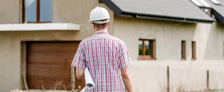 Viser en mann som står klar for å gjøre oppmåling foran en eiendom.