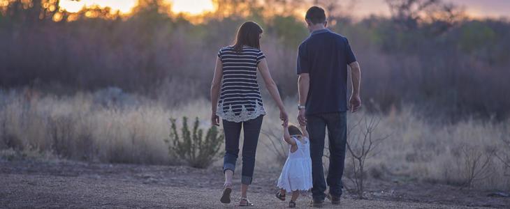 Viser bilde av et par med barn som går hånd i hånd på landet