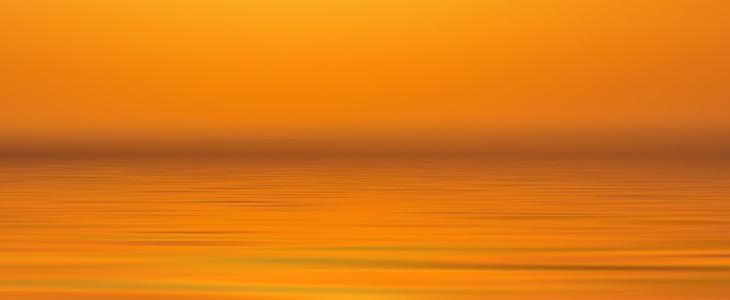 Illustrasjonsbilde som viser fargen oransje som speiler seg i vannet ved solnedgang