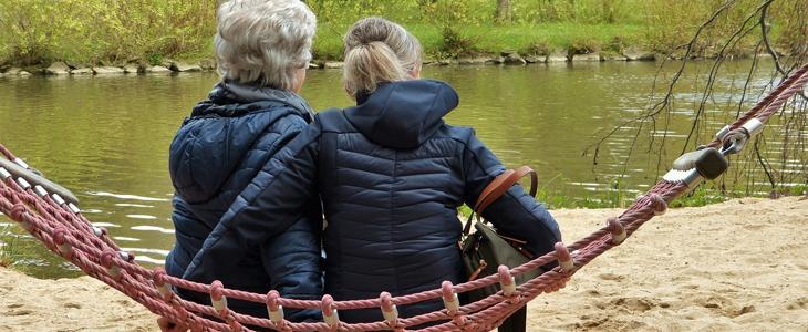 To damer som sitter i ei hengekøye foran en elv.