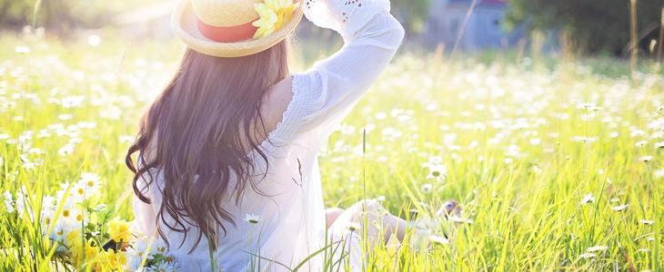 Viser bilde av dame i blomstereng med solhatt
