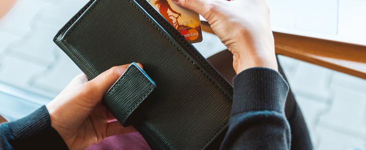 Viser bilde av en som sitter og ser på bankkortet og lommeboka si.