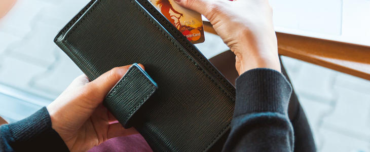 Bildet viser en person som ser på innholdet i lommeboken sin.