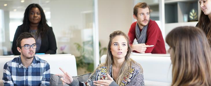 bildet viser menn og kvinner i et kontorfellesskap som snakker sammen