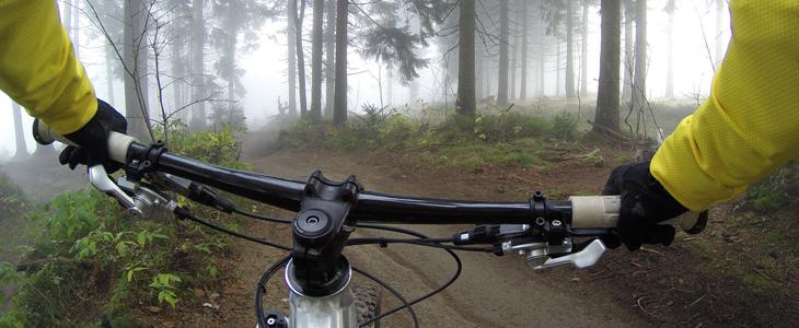 Bildet viser en syklist som sykler innover på en skogsti