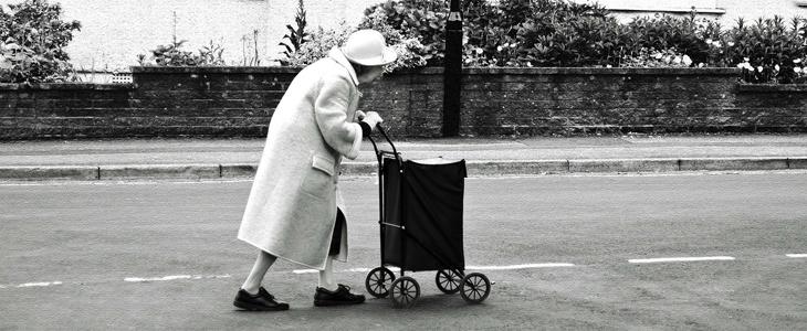 bilde av en gammel dame som går langs vegen med en handletralle