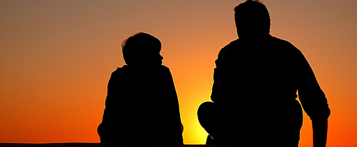 siluette av et barn og en voksen som snakker sammen
