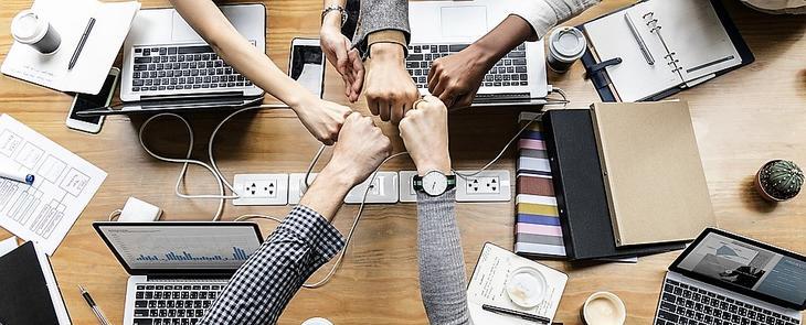 Bildet viser fem personer som samarbeider over et bord.