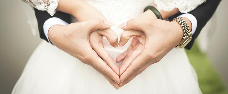 Et par holder hender som danner et hjerte