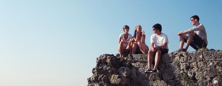 Viser bilde av fire ungdommer som er sosiale og sitter og prater sammen.