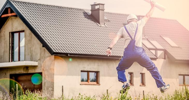 en mann som hopper av glede med byggetegninger