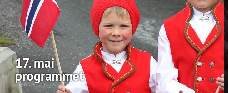 viser bilde av en gutt i bunad med norsk flagg