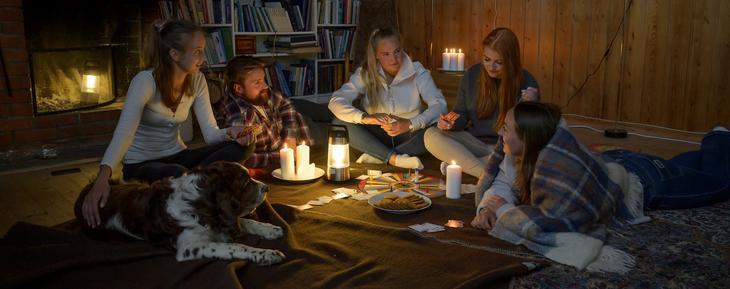 Viser bilde av en familie som er samlet rundt et brettspill. De har tent diverse stearinlys og batteridrevne lykter, da strømmen har gått.