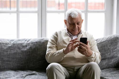 eldre mann som ser på telefonen sin