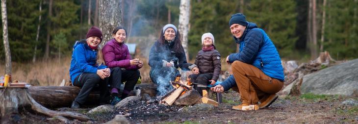 Familie på tur og griller pølser i naturen